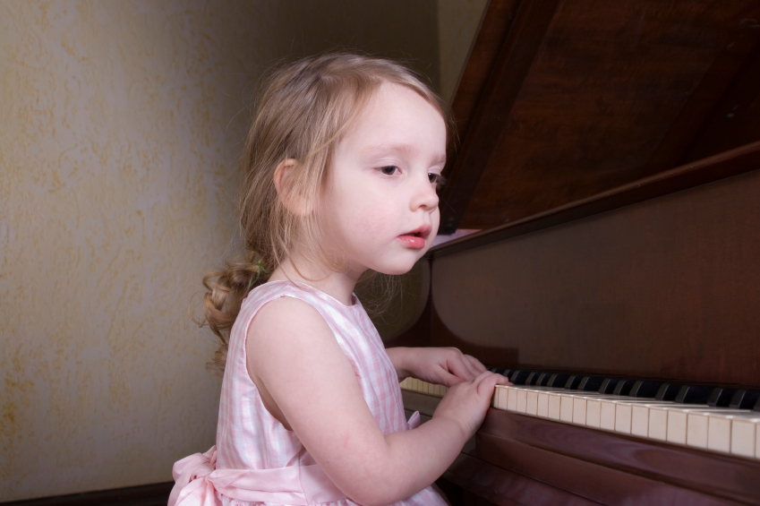 Image of a little girl playing piano
